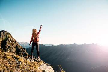 Young woman on the top in the mountains