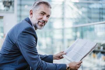 Portrait of smiling businessman reading newspaper