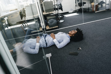 Young woman lying on the floor in office