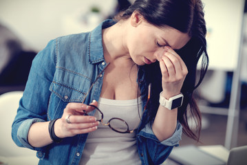 Sad tired woman holding her glasses