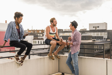Three friends socializing on a rooftop party
