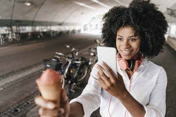 Happy young woman taking cell phone picture of ice cream cone