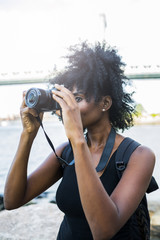USA, New York City, Brooklyn, woman taking pictures at the waterfront
