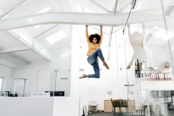 Young woman hanging on beam in office