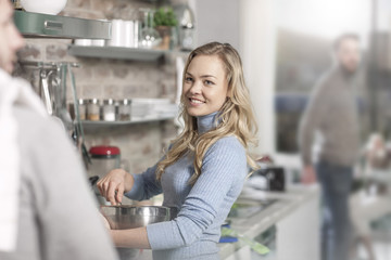 Young woman stirring bowl cooking in kitchen