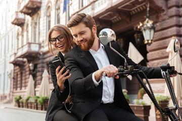 Happy stylish couple sitting on modern motorbike outdoors