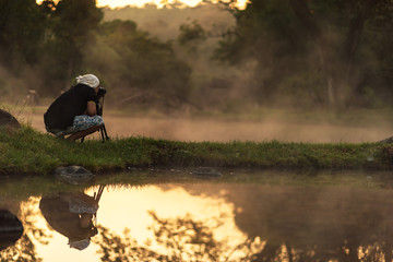 silhouette of photographer taking picture of landscape during sunset. Lifestyle Concept.
