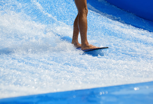 Muscular young athletic boy surfing in the water