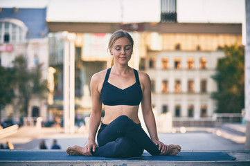 Beautiful young woman practices yoga asana Cow Face pose gomukhasana in the city