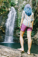 Traveler woman looking at waterfall in summer.