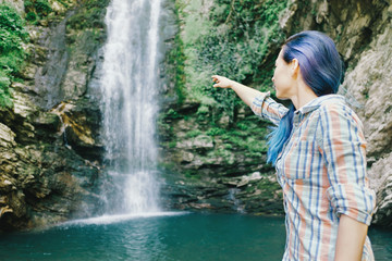 Woman pointing at waterfall.