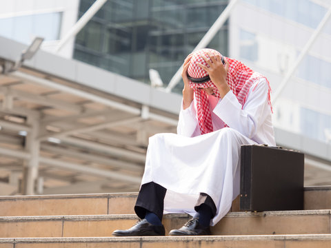 Upset arab businessman sitting at stairs in the modern city, holding head, feeling down, disappointed from business problem concept