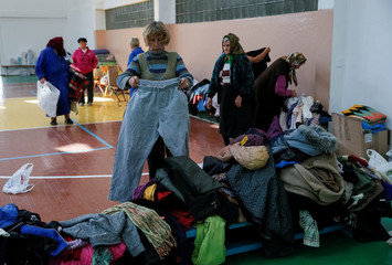 Residents evacuated from villages located near a military ammunitions depot that exploded are seen in the school gymnasium as they pick up clothes from humanitarian aid in Vinnytsia