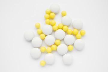 White and yellow pills on white background