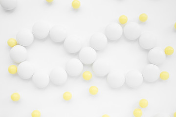 Infinity symbol made of pills , white and yellow pills on white background