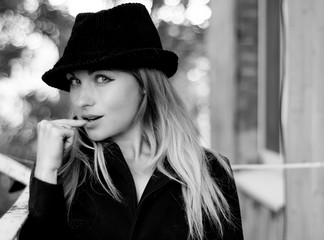 portrait of attractive sensual sexy woman with blond hair and bright makeup in black tweed hat with finger near lips indoor, looking at camera, on blurred backdrop, horizontal picture. Monochrome