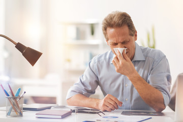Sick adult man blowing his nose