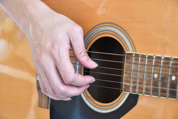 Close-up Hand of young man playing acoustic guitar at home