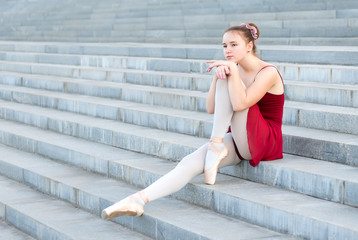 Ballerina girl sits on the steps in a ballet dress