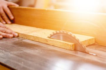Carpenter cutting wooden board with circular saw.