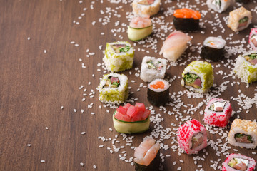 Set of sushi, maki and rolls with sesame on wooden rustic background