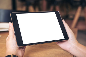 Mockup image of hands holding black tablet pc with blank white screen with coffee cup on wooden table in cafe
