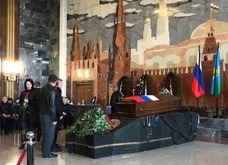 People pay their respects next to the coffin containing the body of Russian Lieutenant-General Valery Asapov who was killed by Islamic State shelling near Deir al-Zor, during his funeral ceremony at a military cemetery outside Moscow