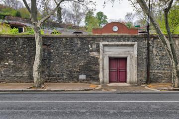 Closed old red wooden door, stone wall, and trees at Ciragan Street, Beshektash, Istanbul, Turkey