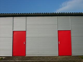 Rote Stahltüren in einem modernen silbernen Flugzeughangar am Segelflugplatz in Oerlinghausen im Teutoburger Wald in Ostwestfalen-Lippe
