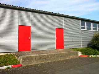 Rote Sicherheitstüren in einer modernen Lagerhalle mit Fassade aus Wellblech am Segelflugplatz in Oerlinghausen in Ostwestfalen