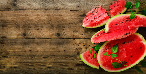 Slices of watermelon with mint leaves on wooden background. Detox and vegetarian concept. Top view, flat lay, copy space, banner