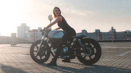 Outdoor lifestyle portrait of sexy biker girl on a modern motorcycle on a top of a building, sunset over city in the background