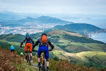 Basque mountain bikers descending into the distance towards San Sebastian