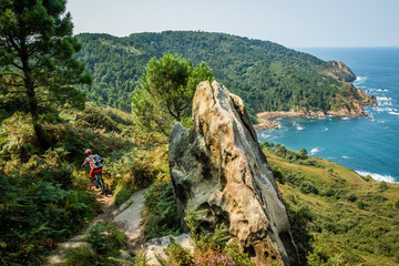 basque coast mountain biker riding along the coastal trail with sea and forest behind