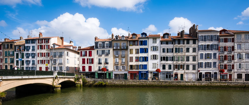 Old narrow houses in front of the river Adour, Bayonne, France