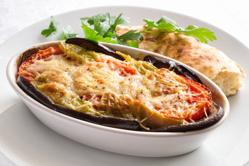 moussaka covered with grated cheese and served with pita bread and parsley