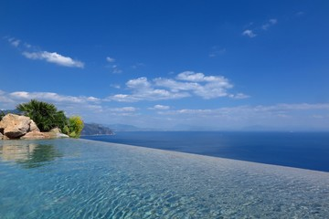 infinity pool view overlooking sea on sunny blue sky day with copy space