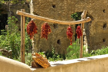 sun dried tomatoes hanging in the sun with rustic stone wall backdrop