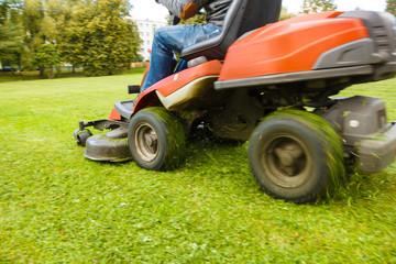 the lawn mower drives through a green meadow