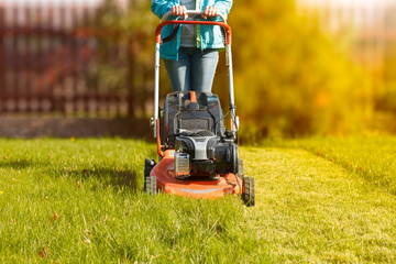 woman working with a lawnmower in the garden