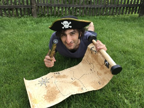 Pirate with a treasure map lying on the grass
