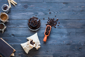 Coffee beans and cup of coffee with other components on different wooden background.