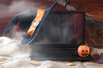 The concept of Halloween: a laptop, a witch hat and a broom, free space for your advertising.