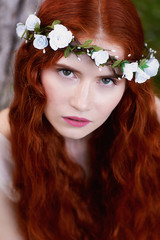 Portrait of a beautiful redheaded girl with long curly hair. Bride. With handmade jewelry on the hair. Hair to the waist. Very long red hair. Big facial