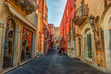 Old street in Taormina, Sicily, Italy. Architecture with archs and old pavement.