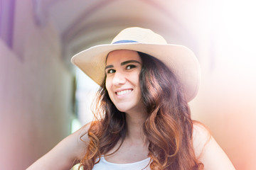 Girl with hat on summer day in the street. Happy smiling face.