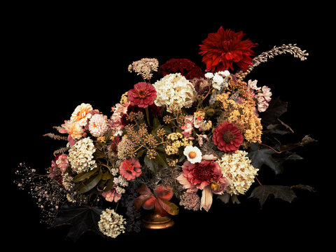 Floral arrangement, autumn bouquet, on black background. Toned image.