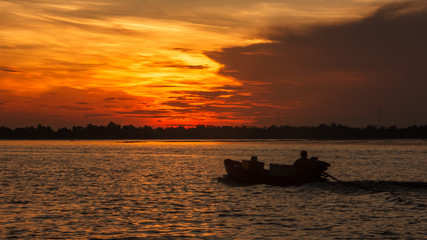 Boat Riding Silhouette on the morning sunrise in Hau River, a distributary of the Mekong river, Can Tho, Vietnam, Indochina, Asia.