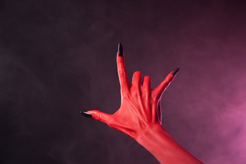 Red devil hand with black nails showing heavy metal symbol