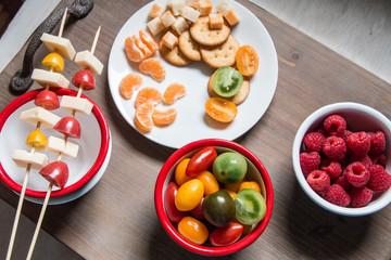 Snack idea - berry, tomato, crackers and cheese in enameled bowls